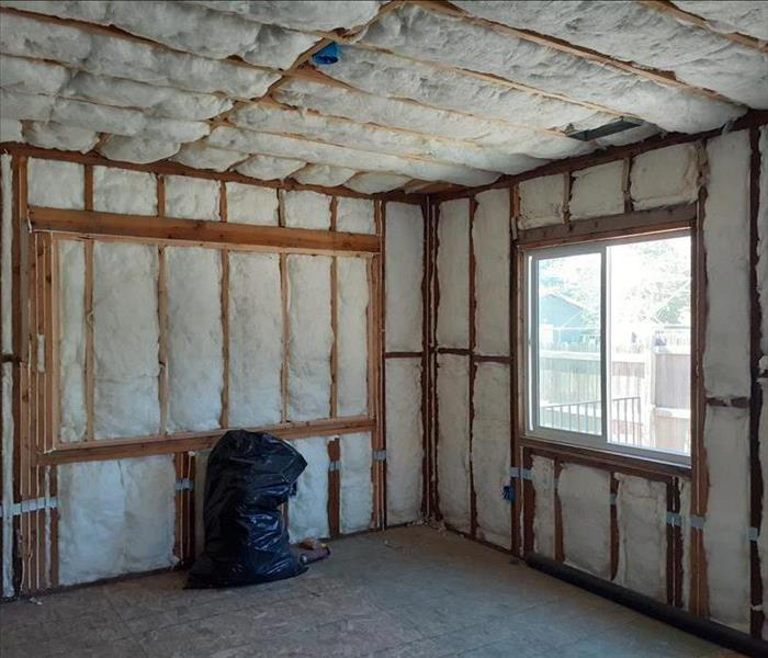 A room with out walls showing framing and white insulation.