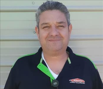 Gustavo wearing his black SERVPRO shirt smiling.