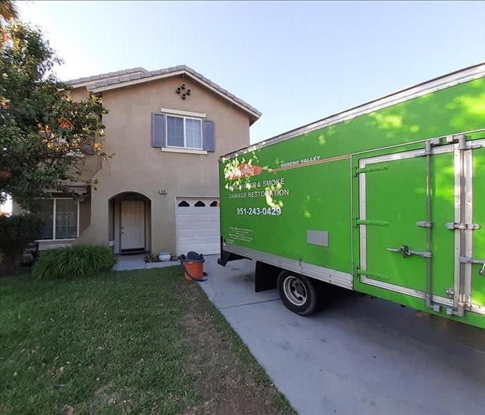 Our green SERVPRO Truck sitting in front of a 2 story home.