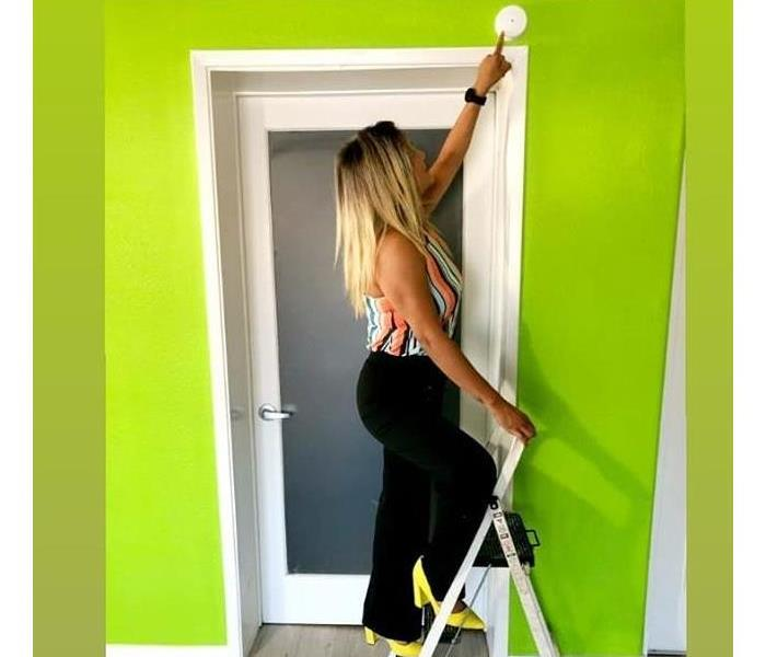 Nancy wearing her banana yellow heels while on a step ladder pointing to a smoke detector. Green wall in the background.